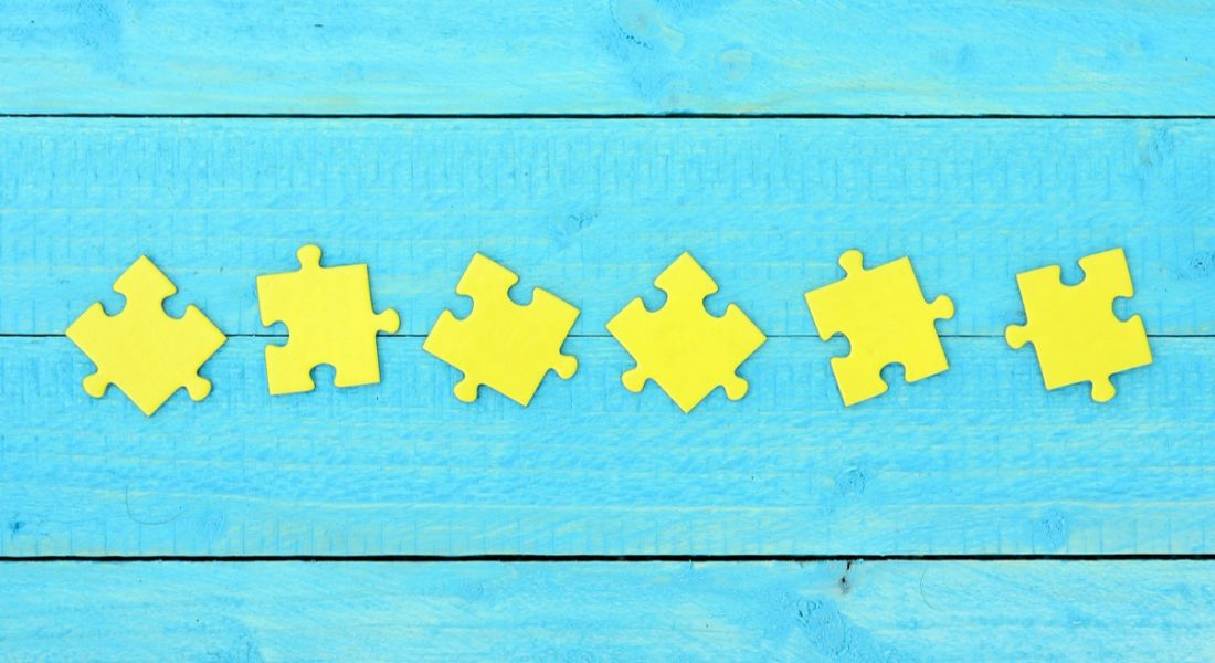 Six yellow jigsaw pieces arranged on a sky-blue wooden background.