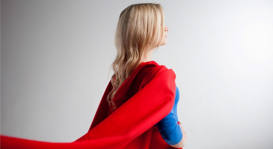 A blonde woman in a blue top, red skirt and red cape stands with her back to the viewer.