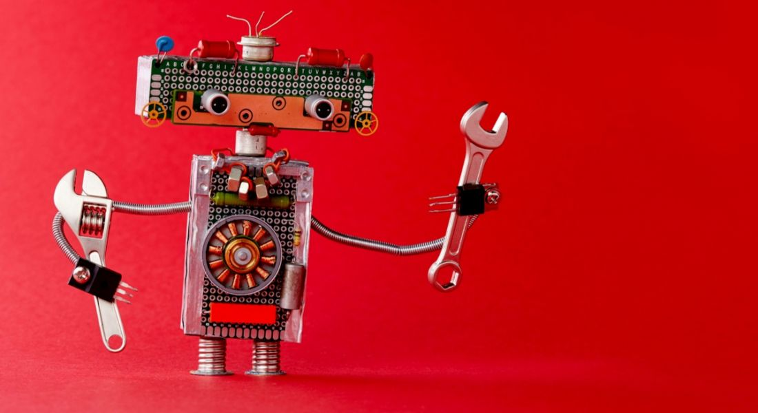 A cute silver toy robot holds a wrench in each arm aloft against a red backdrop.