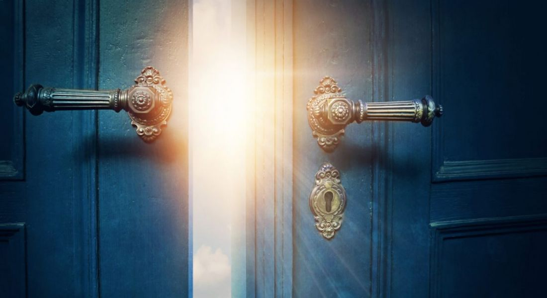 Two vintage navy blue doors with gold handles opening to reveal sunshine, depicting breaking into cybersecurity.