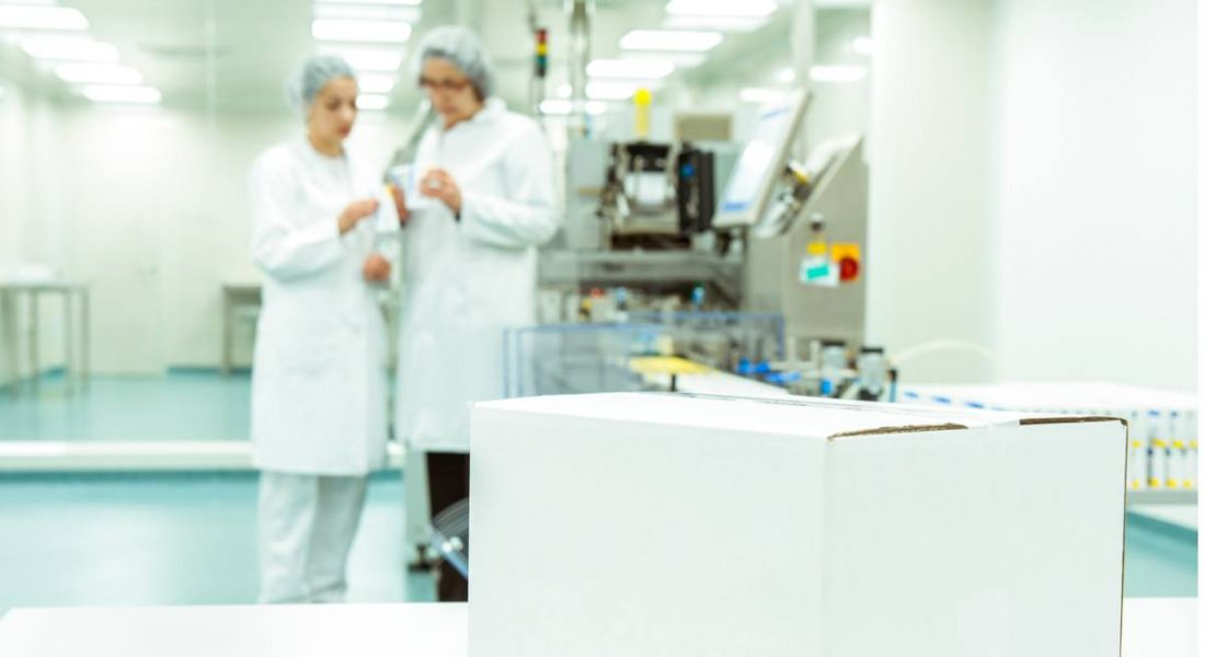 white box on table in forefront with two pharma workers in blurry background wearing lab coats and hair nets.