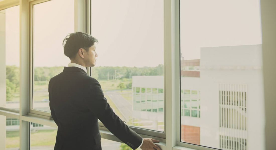 A young man in a dark business suit staring pensively out a floor-to-wall window thinking about the future of work.