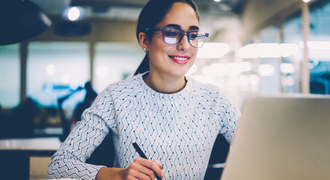 Young woman with glasses smiling at a laptop. She's writing down the future of work influencers she needs to follow.