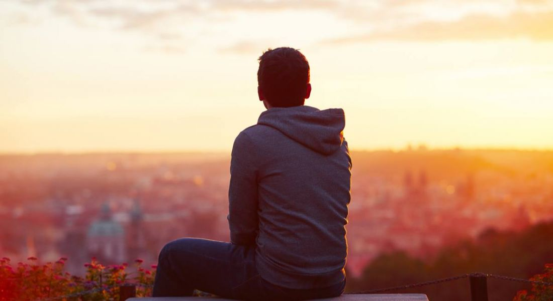 A young man wearing a hoodie. His back is to camera and he is looking at a sunrise and thinking about his life experiences.