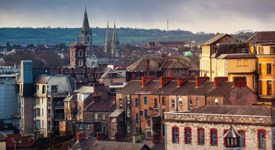 A vantage point view of an old part of Cork city, with a church and rolling emerald hills in the background.