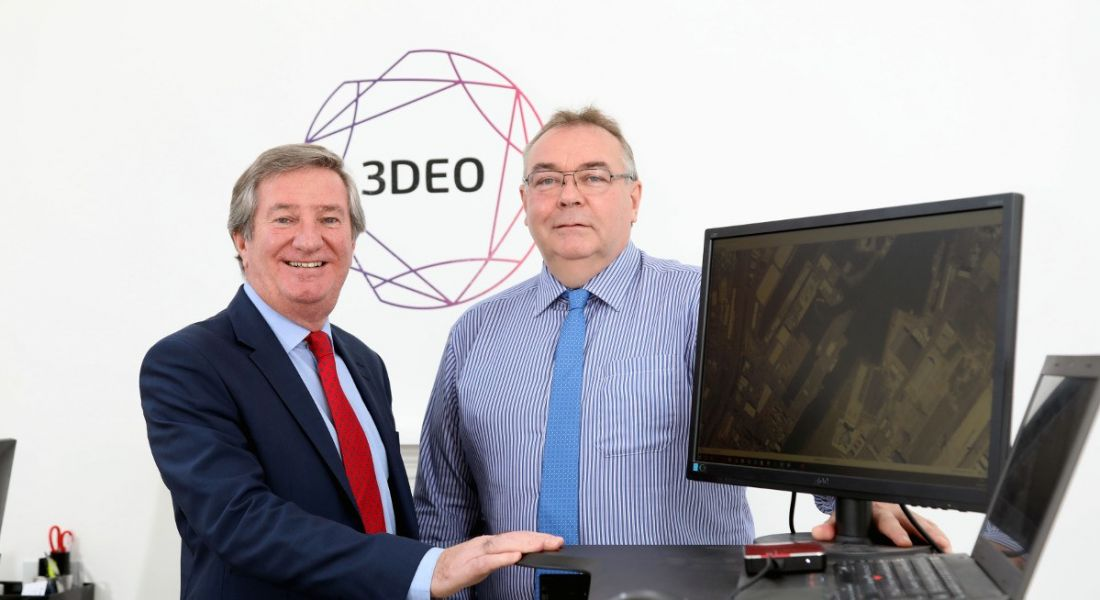 Two middle aged men in shirts and dies standing next to a desktop in front of a geometric logo with '3DEO' inside it.