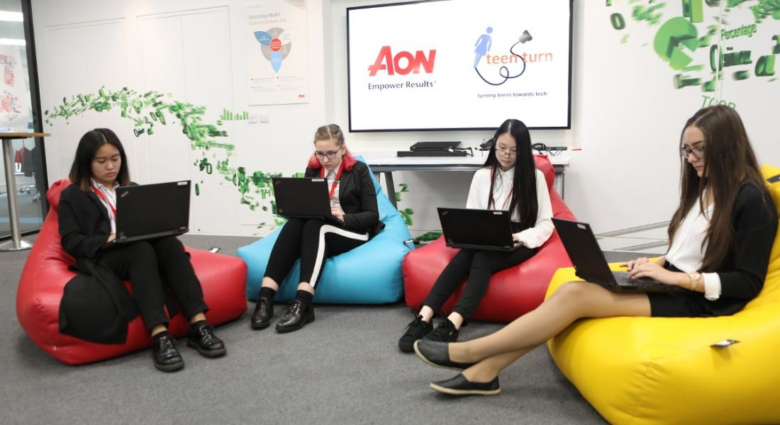 Four young women sit on bean bags while looking intently at their laptops.