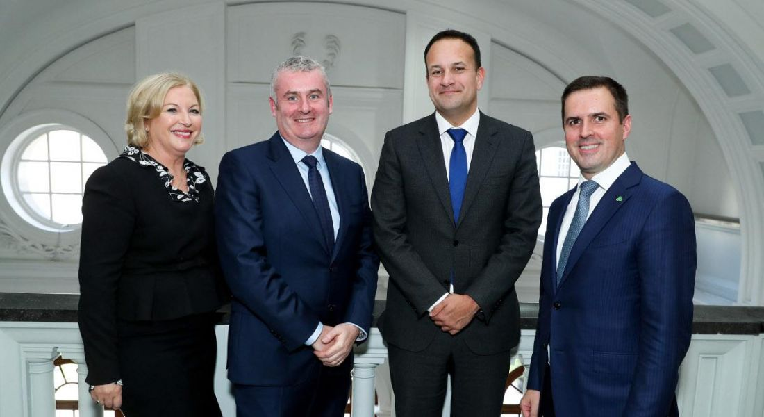 A blonde woman in a black skirt and blazer and three men in suits standing in a line smiling at the MSD jobs announcement.