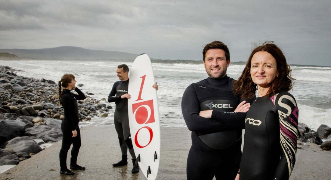 Two women and two men in surf gear on a Sligo beach.