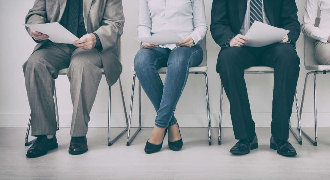 A view of the lower half of business people sitting on chairs waiting to be interviewed for a job.