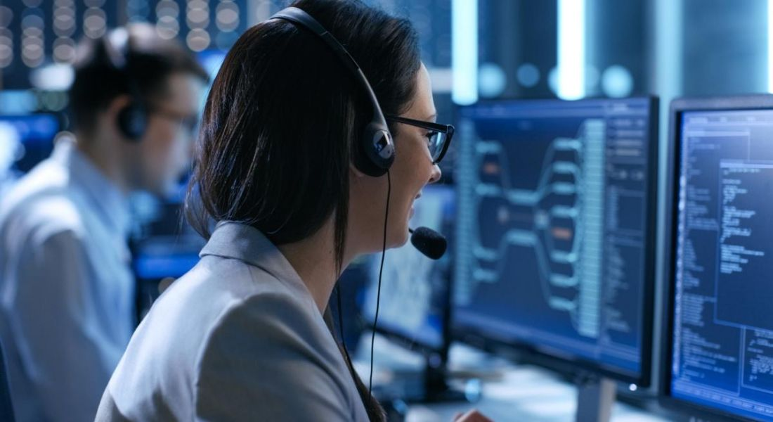 The back of the head of a dark-haired woman with glasses wearing a head set and looking at a computer screen while working in a technical support role.