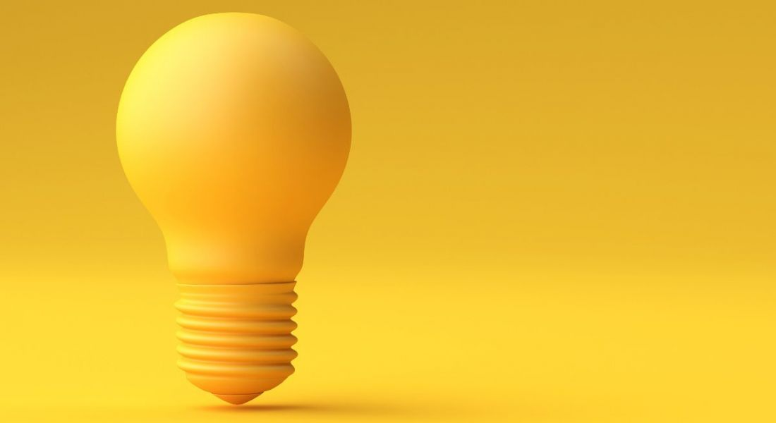 A yellow lightbulb standing alone against a yellow background, representing brainstorming as a concept.