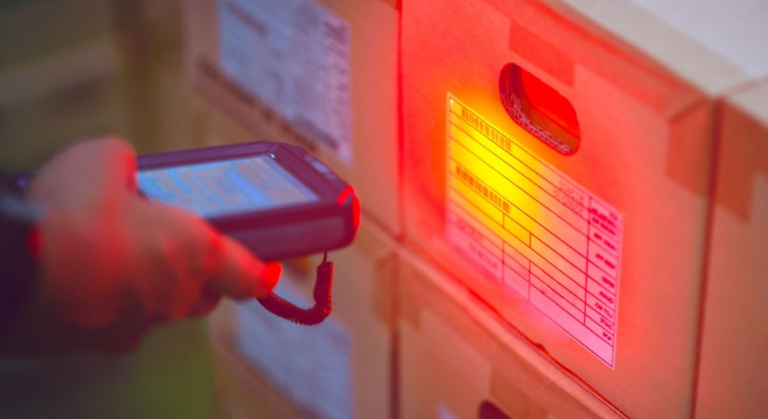 A man holding a handheld scanner beaming a red light onto a barcode on a box in a warehouse.