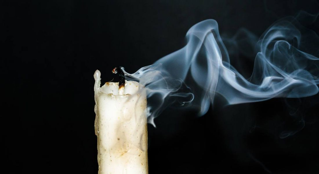 A lone, white candle burnt out, leaving a trail of smoke against a black background. It depicts employee burnout.