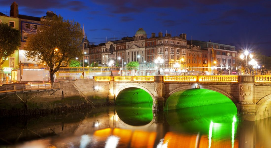 A river veining through the city of Dublin illuminated at night with green and orange lights. Dublin's iconic Georgian style architecture can be seen.
