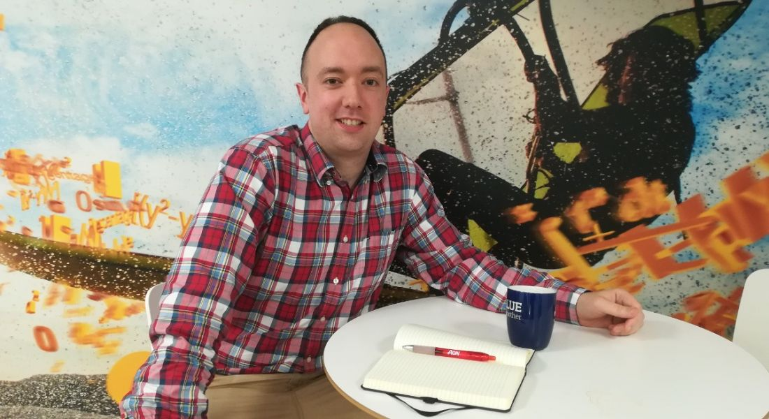 A man with short, dark hair in a check shirt sitting at a table with a mug and open notepad smiling at the camera.
