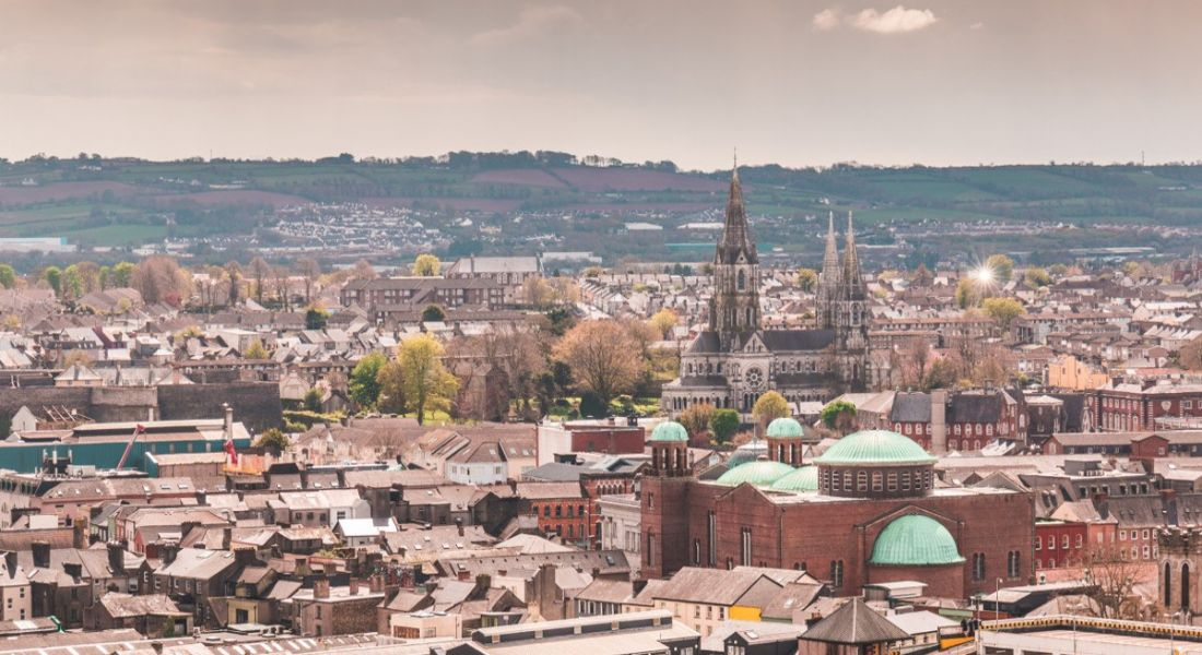 A panoramic view of Cork city with hills behind it.