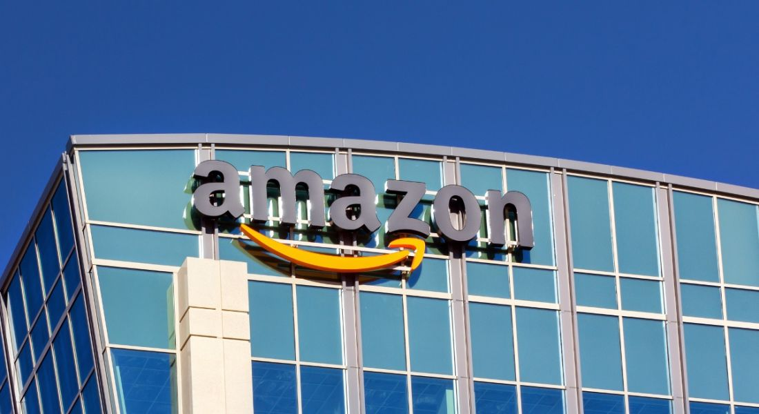 An image of the Amazon company logo on a glass building on a sunny, clear morning in Santa Clara, California.