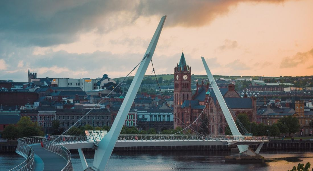 A view of Derry city from the Peace Bridge under a cloudy sky.