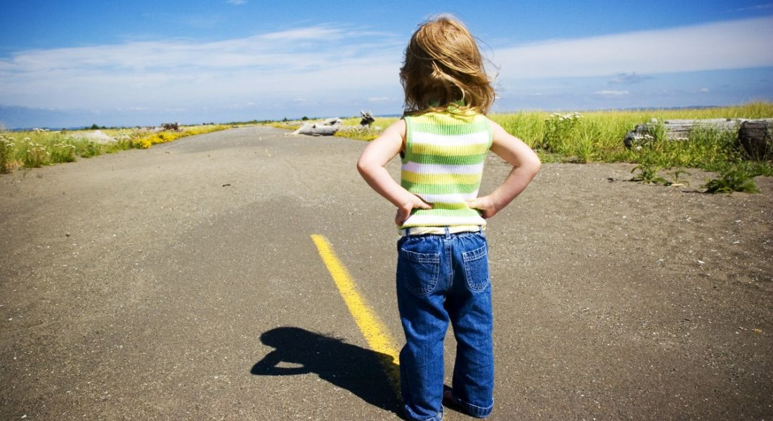 A little girl facing a long road with her hands on her hips. She means business when it comes to the future of work.