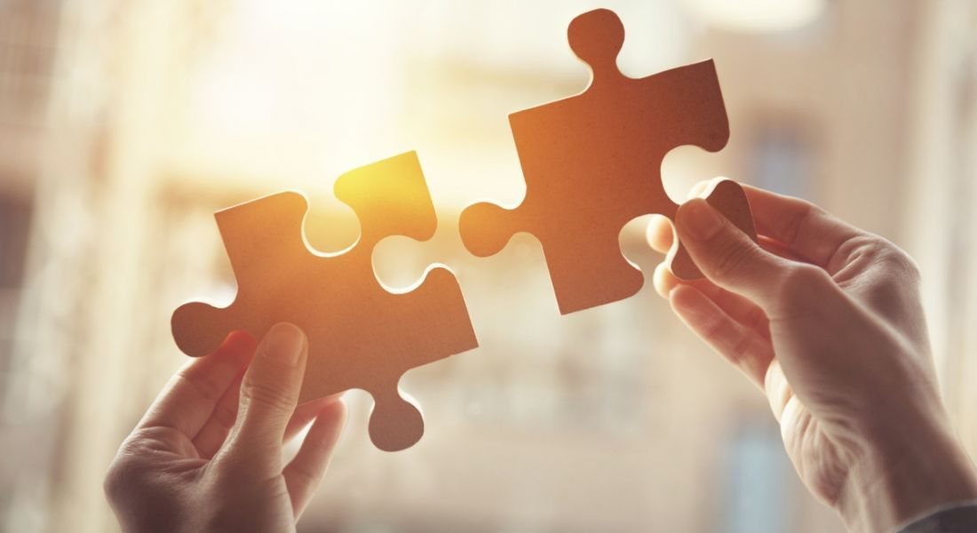 Two hands holding up two large jigsaw pieces against orange sunlight, representing company culture fit.