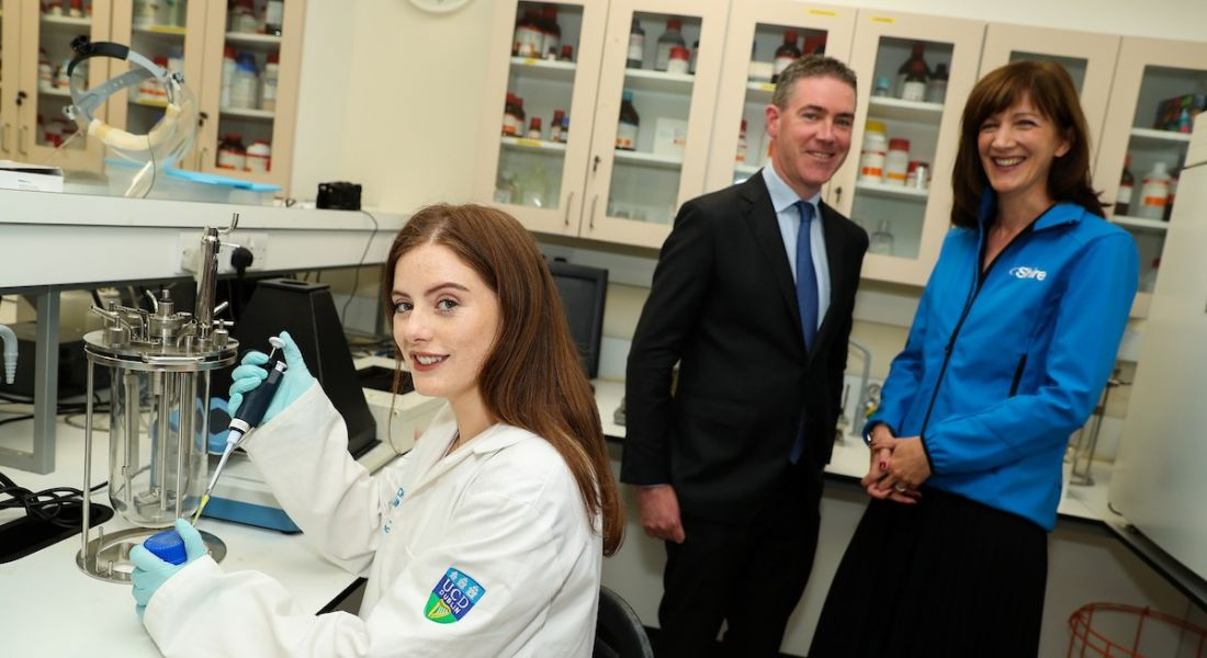 A brunette student holds lab equipment while a man in a suit and a woman with a Shire sweatshirt smiling in the background.