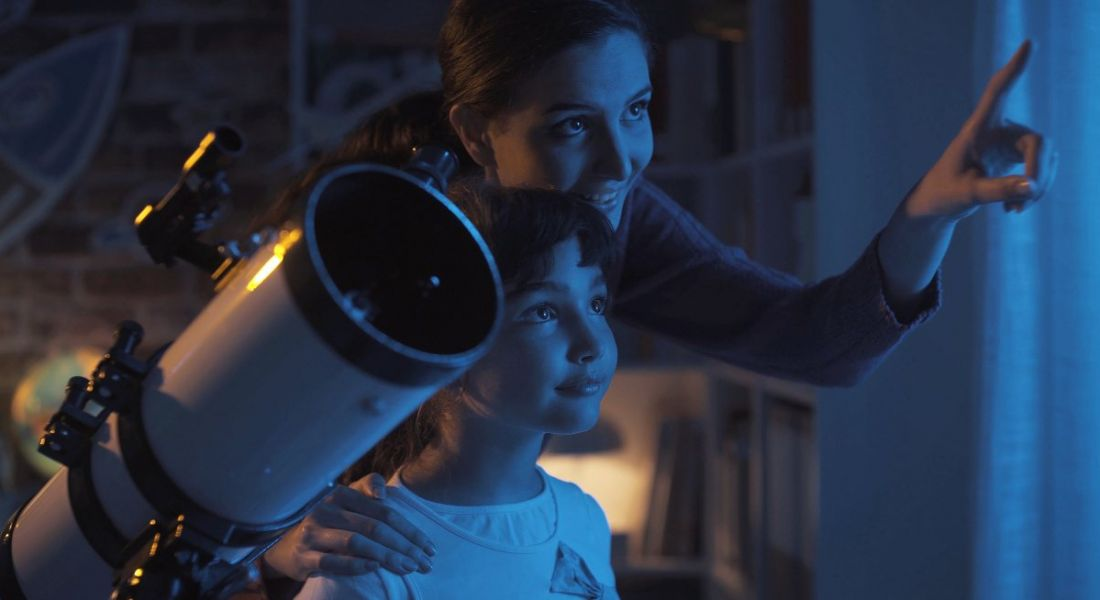 A woman with a young girl smiling and pointing out at the sky, standing beside a telescope dreaming about space careers.