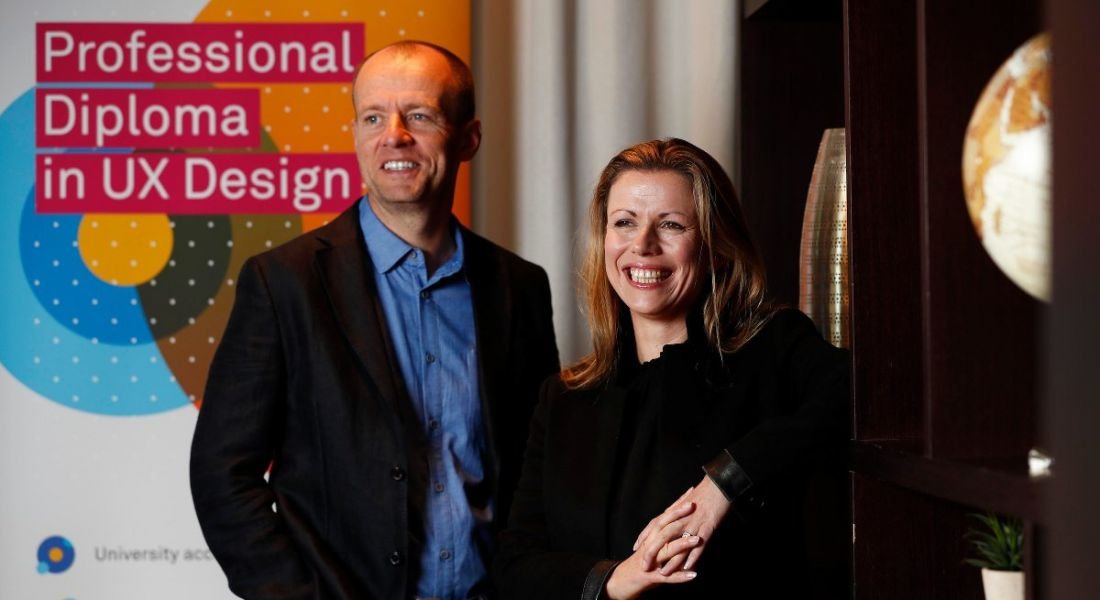 A ginger haired man and blonde woman smiling while looking off to the side at a UX Design Institute launch
