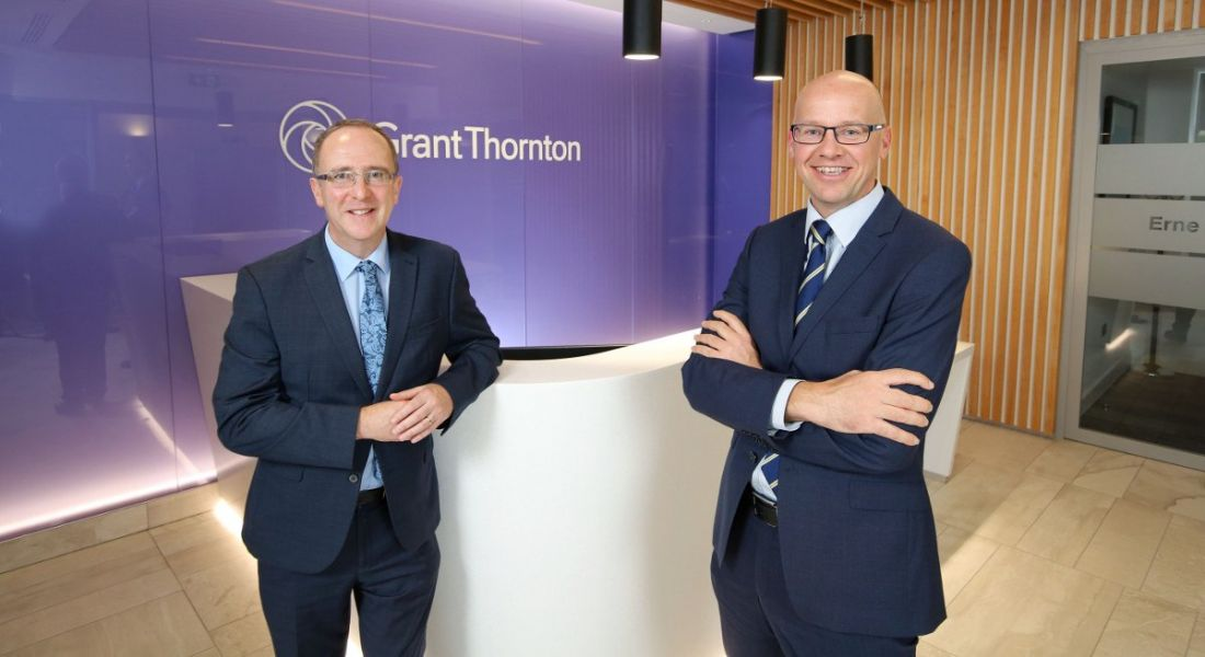 Two suited glasses wearing men smiling at the camera against a purple wall emblazoned with company name Grant Thornton.