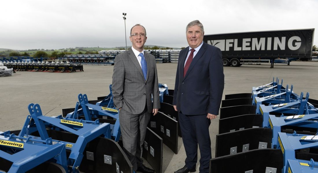 Two suited men smiling and standing among ground-level machinery manufactured by Fleming Agri.