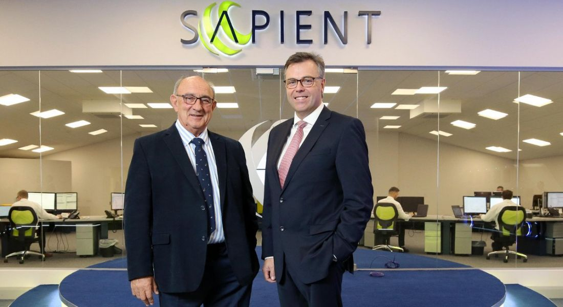 Two men in suits, the CEOs of Camlin and Invest NI respectively, smiling under a green sign that says 'Sapient'.