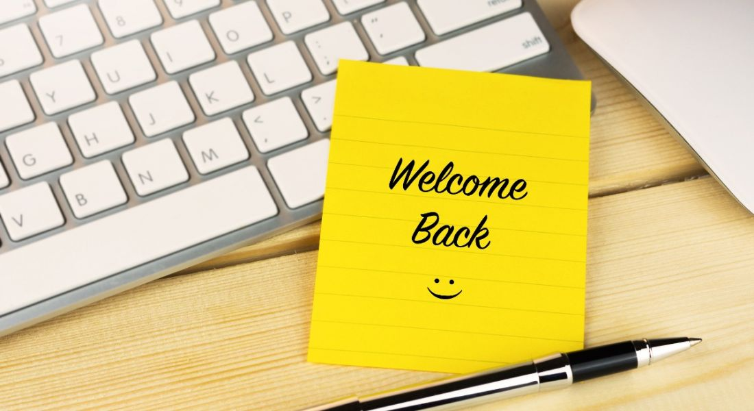 A yellow sticky note on a keyboard reads 'Welcome Back' with a smiley face.