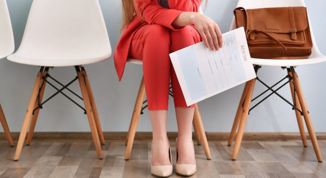 View of a woman's legs and a hand cliutching as résumé as she sits in a waiting room before a job interview.