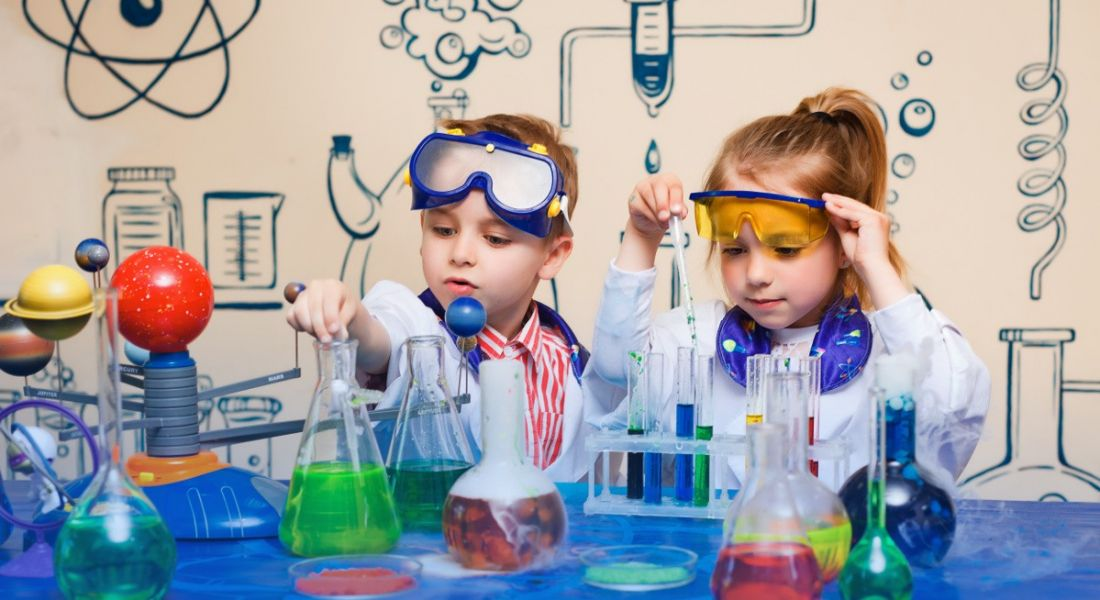 A young boy and girl dressed as scientists, playing with an assortment of beakers, dreaming of a science career.
