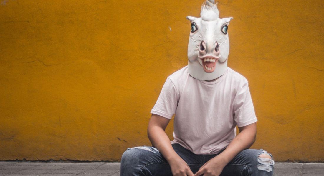 Man in unicorn mask sitting against yellow wall.