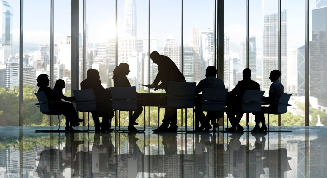 Silhouette of businesspeople crowded around a table in a meeting in a room with ceiling-to-floor windows.