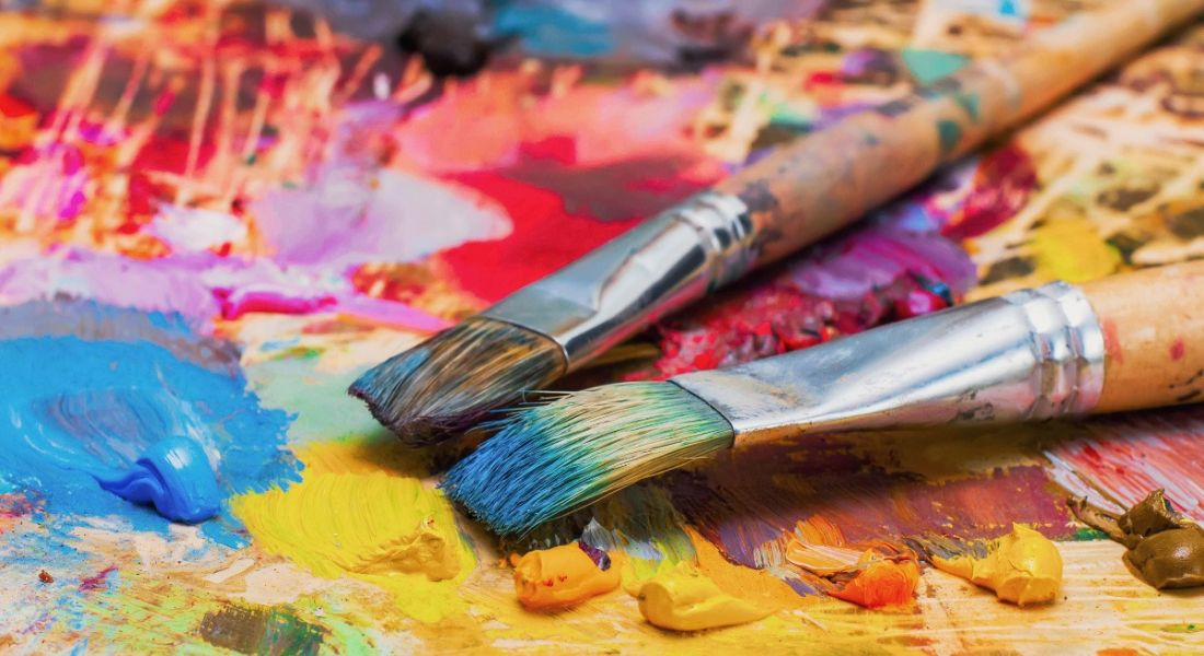 Used brushes on an artist's palette of colourful oil paint for drawing and painting.