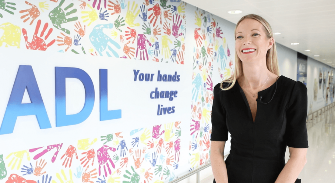 A blonde woman in a black dress smiling, standing beside a large sign with a lot of colourful handprints on it in Amgen.
