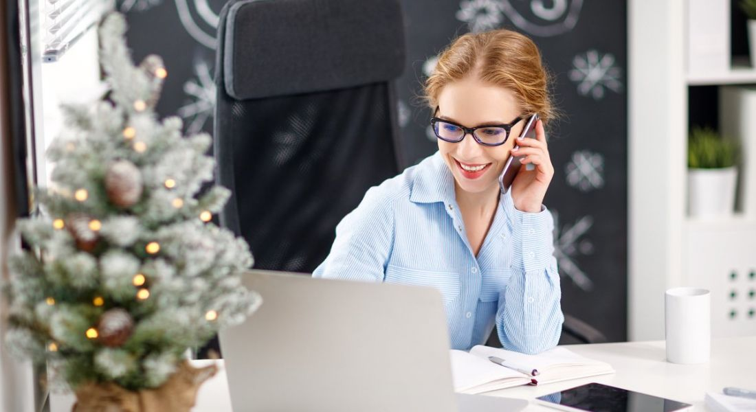 A smiling attractive woman working at a laptop with a small Christmas tree on her desk. She knows how to get organised.