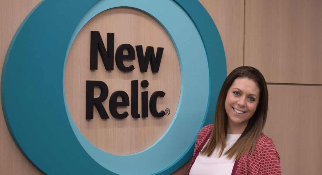 A brunette woman smiling with her head cocked to the side standing in front of a New Relic logo on a wall.