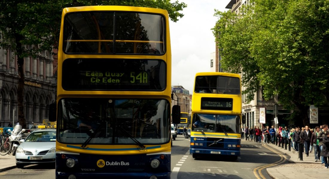 Two Dublin buses driving down a main street in Dublin city on a bright, clear, cloudless day.
