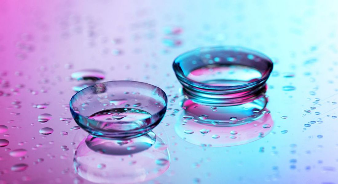 Contact lenses surrounded by water droplets on pink-blue background.
