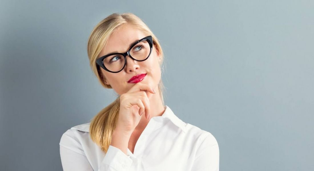 A blonde woman wearing a white shirt and glasses rests her chin on her hand thinking about the future of work.