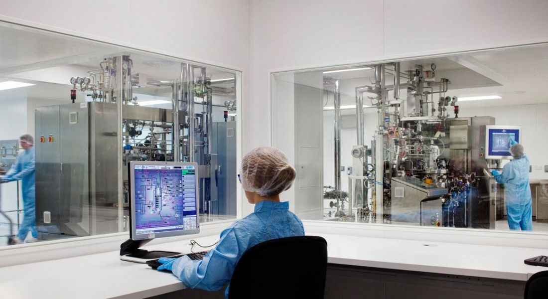 A woman with a science job in a blue lab coat sitting at a laptop in a lab office. Other scientists work in the background.