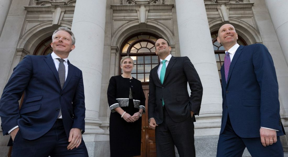 three men in dark suits and a woman in a dark dress stand outside government buildings in Dublin.