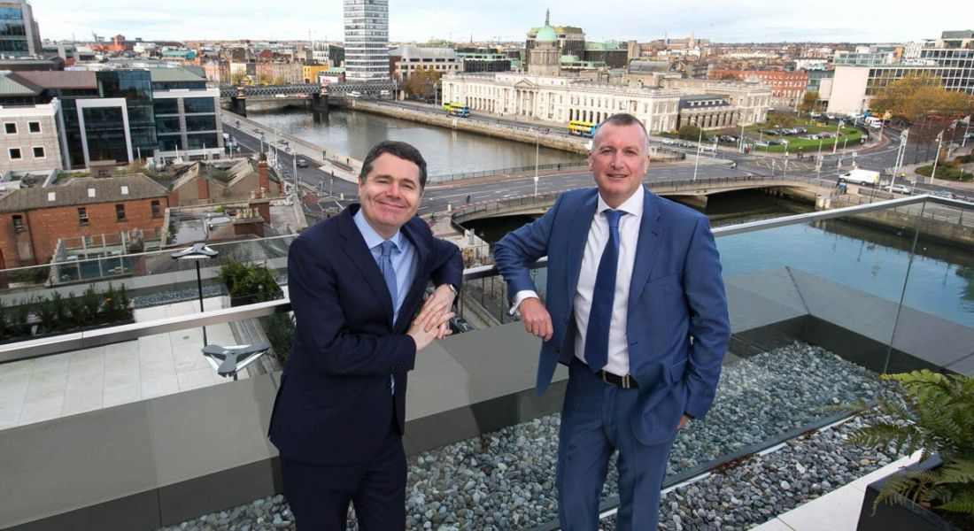 Two men leaning against the railing of a rooftop terrace overlooking Dublin at Grant Thornton offices.