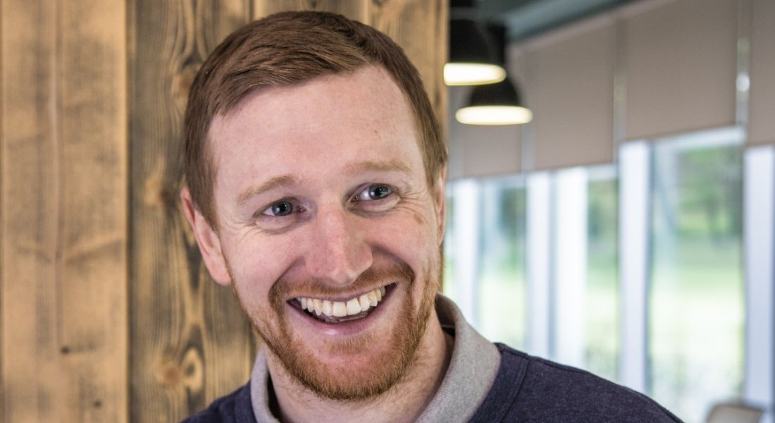 A headshot of a smiling man with red hair and a short beard in a blue jumper. He works for Fidelity Investments.