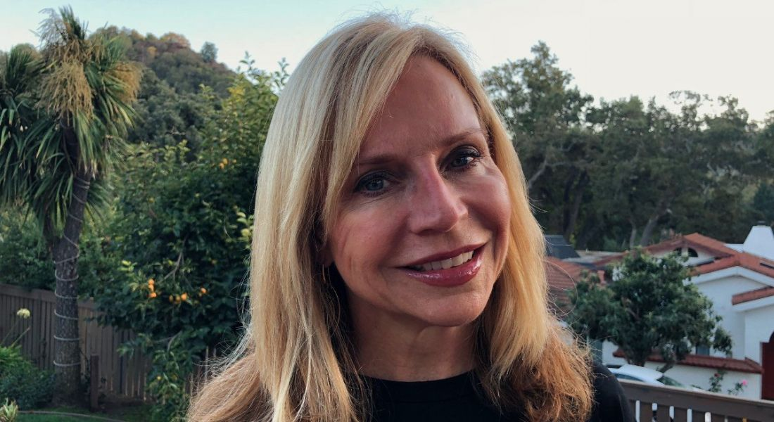 A blonde smiling woman against a scenic outdoor background. She is the CHRO of Symantec.