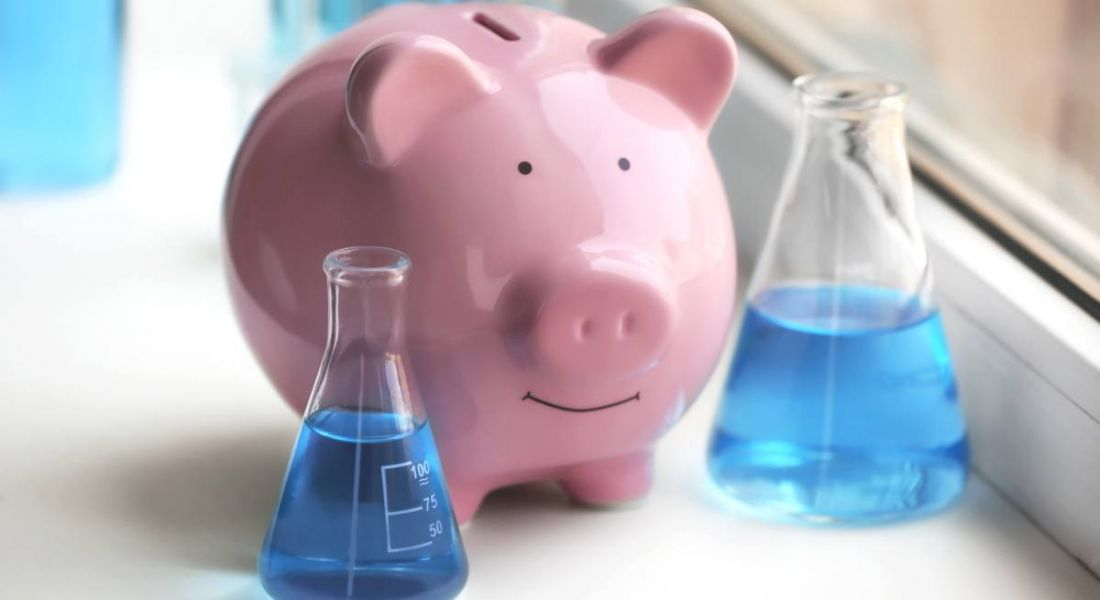 A pink piggy bank standing beside two lab beakers with blue liquid, representing salaries in life sciences.