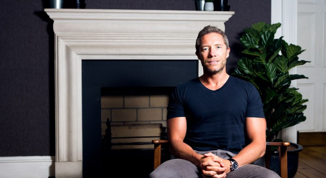 man with his arms held in his lap sitting and looking into the camera against the backdrop of a navy wall, sprightly potted ferm and white fireplace.